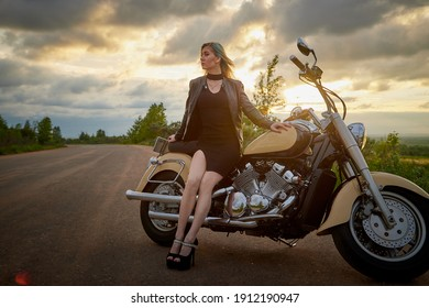 Attractive female brunette motorcyclist with motorcycle in a summer evening during sunset. Beautiful girl on nature and sky with sun and clouds background. Adventure and travel concept