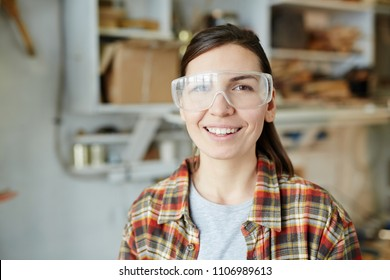 Attractive female carpenter in protective glasses smiling and looking at camera while standing in workshop.
