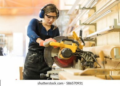 Attractive female carpenter using some power tools for her work in a woodshop