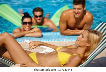 Attractive female and companionship by pool at summertime.