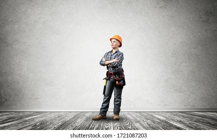 Attractive female construction worker in hardhat standing with folded arms. Confident young specialist in checkered blue shirt and jeans standing in empty room. Interior design and renovation service.