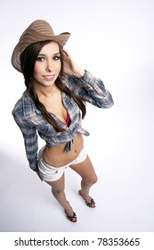 Attractive Female Cowgirl Standing Shorts Plaid Top Touching Cowboy Hat