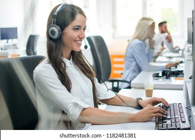 Attractive female customer support telephone operator working in call center