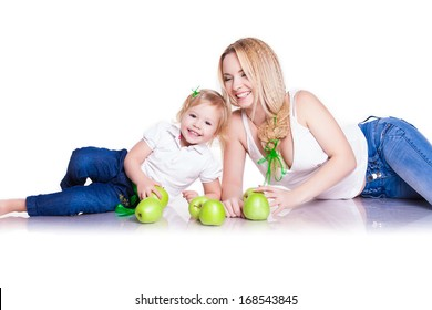 Attractive female with cute baby girl, closeup portrait of young mother and her little daughter with green apples, studio shot, happy family, child care and love concept