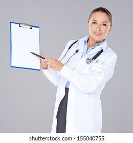 Attractive female doctor in a lab coat displaying a blank clipboard in front of her chest and pointing to it with a pen  isolated on grey