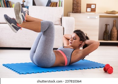 Attractive female doing exercise in her living room.She doing abs.Workout.