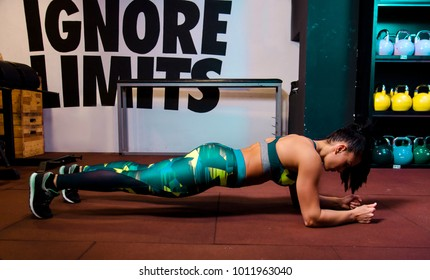 Attractive female doing plank exercise in gym