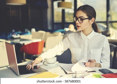 Attractive female economist in elegant outfit checking documentation and reports of restaurant incomes working with database making statistics and amount of costs using modern technologies