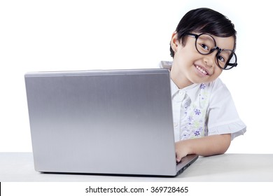 Attractive female elementary school student smiling at camera and using a laptop, isolated on white background