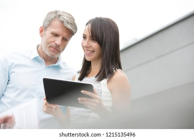 Attractive female employee is holding a black tablet PC with greg haired senior worker is also looking at the data on the screen,
