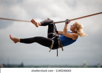 Attractive female equilibrist hanging on the slackline rope upside down on the background of clear sky