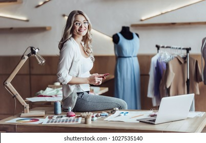 Attractive female fashion designer is working in her workshop. Stylish woman in process of creating new clothes collection.
