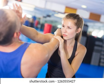 Attractive female is fighting with trainer on the self-defense course for woman in sport club