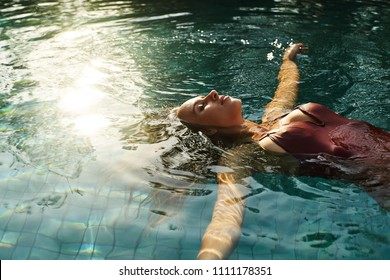Attractive female floating on swimming pool water surface in sun light