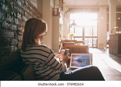 Attractive female freelancer chatting with her friends  while sitting front open computer in vintage coffee shop