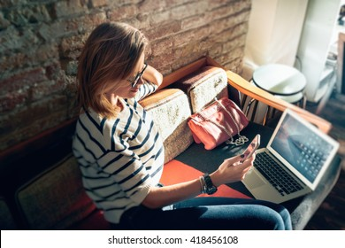 Attractive female freelancer chatting with her friends  while sitting front open computer in vintage coffee shop. Young modern business woman working remotely over a new start-up project.