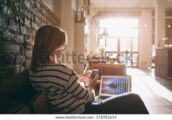 Привлекательная женщина фрилансер в чате со своими друзьями сидя перед открытым компьютером в винтажном кафе