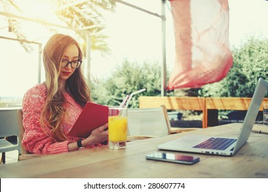 Attractive female freelancer reading notebook while sitting at wooden table front open computer in modern coffee shop, young creative woman work on laptop while having breakfast on terrace, flare sun