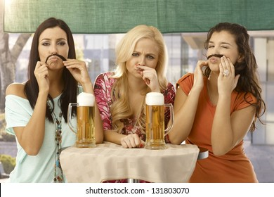 Attractive female friends having fun, forming moustache from hair, drinking beer.