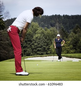 Attractive female golf player putting on green with second player in the background.