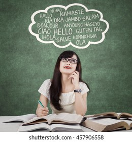 Attractive female high school student learns foreign language in the classroom with books
