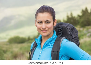 Attractive female hiker with backpack smiling at camera in the countryside