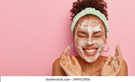 Attractive female model with crisp combed hair, closes eyes and gestures actively, feels pleased, washes face with cleansing foam, wears headband, wants to have well cared complexion and skin