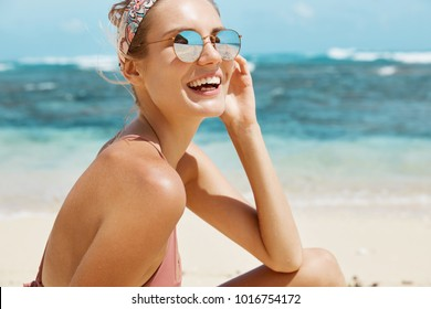 Attractive female model wears headband and sunglasses, has perfect slim body, smiles happily at camera, looks aside into distance, admires beautiful marine landscapes, fresh air, has vacations