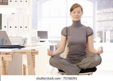 Attractive female office worker practicing yoga, meditating at lotus position.