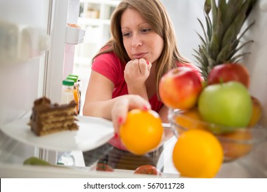 Attractive  female on diet in dilemma whether to eat piece of chocolate cake or orange from fridge