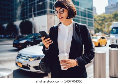 Attractive female owner of bank reading incoming message on smartphone while standing on street near traffic, brunette female employee chatting online with business partners during work break