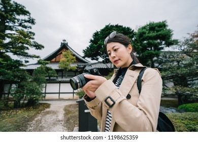 attractive female photographer looking at the photo she took by her slr camera. Young asian photography hobby lover focused taking photos with slr camera. lens man travel in Japan lifestyle.