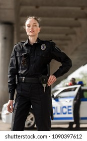 attractive female police officer in uniform looking at camera with blurred partner near car on background