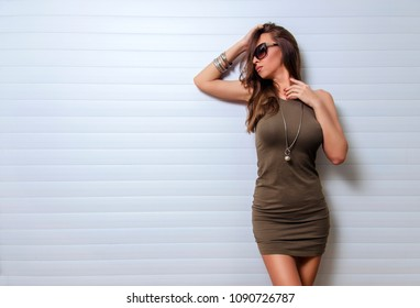 Attractive, female posing in front of white pattern background in summer dress