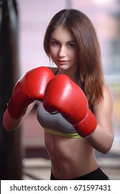 Attractive Female Punching A Bag With Boxing Gloves On