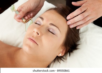 Attractive female reciving face massage with jade roller at acupuncturist