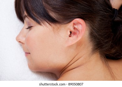 Attractive female relaxing while receiving an acupuncture treatment on the ear