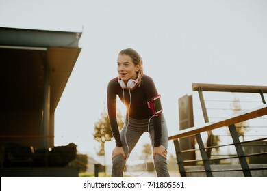 Attractive female  runner taking break after jogging outdoors