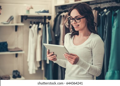 Attractive female shop assistant in eyeglasses is using a digital tablet and smiling while standing in boutique