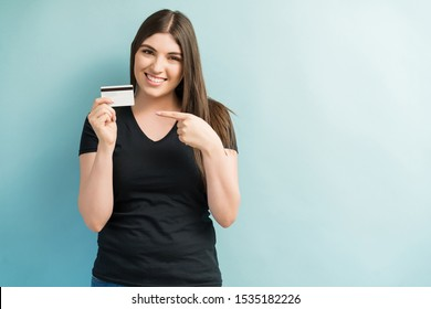 Attractive female smiling while pointing at credit card against plain background