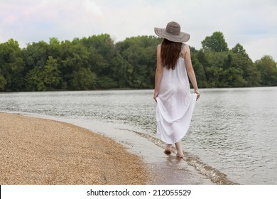 An attractive female strolls along the waters edge.