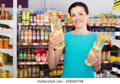 Attractive female in the supermarket want to buying bottle of oil