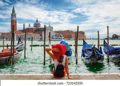 Attractive, female tourist enjoys the view from St. Mark's Square in Venice, Italy