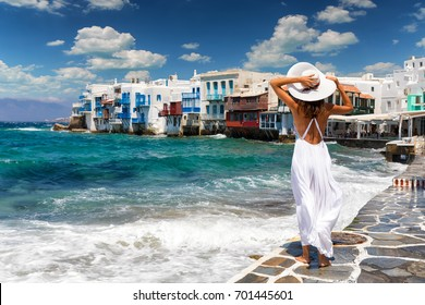 Attractive female tourist with white dress is overlooking famous Little Venice on Mykonos island, Greece