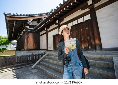 attractive female travler holding a guidemap and visiting the traditional japanese architecture.