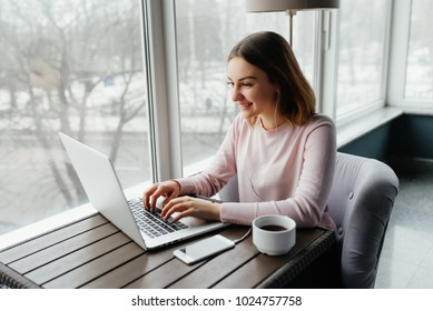 Attractive female is typing messages on a laptop while sitting against the wide windows of a coffee shop. Beautiful girl is working on a portable computer in a cafe.