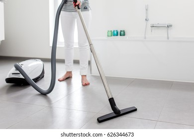 Attractive Female with Vacuum Cleaner in Bath Room