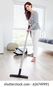 Attractive Female with Vacuum Cleaner in Bedroom