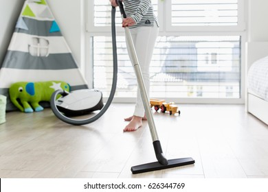 Attractive Female with Vacuum Cleaner in Playroom