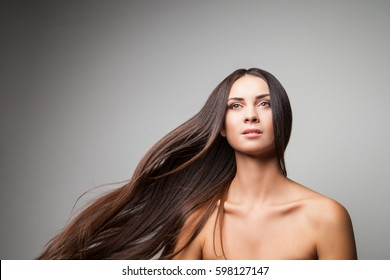 Attractive female with waving long hair looking away. Horizontal studio shot.